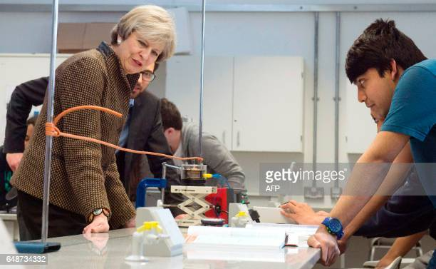 British Prime Minister Theresa May watches a physics experiment during her visit to King's College London Mathematics School in central London on...