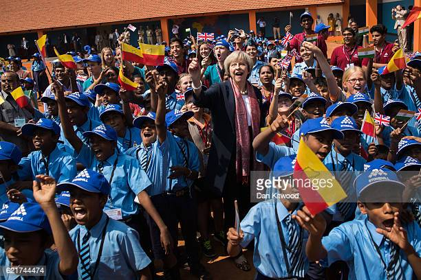 British Prime Minister Theresa May waves a flag as she watches a flypast by the Indian Airforce with children at Stonehill Government Primary School...