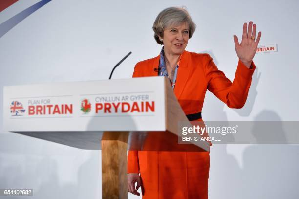 British Prime Minister Theresa May waves to delegates as she leaves the stage after delivering her address at the Conservative Party Spring...