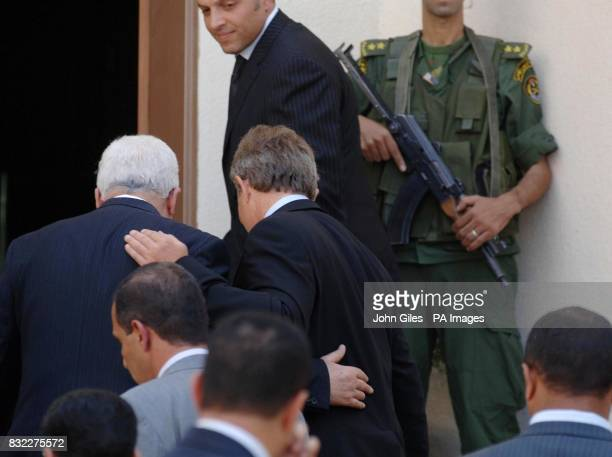 British Prime Minister Tony Blair and Palestinian President Mahmoud Abbas put their arms around each other as they enter the Presidential Compound in...