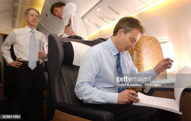 British prime Minister Tony Blair studies papers en route to the Azores where he will hold talks with American President George Bush and Spanish...