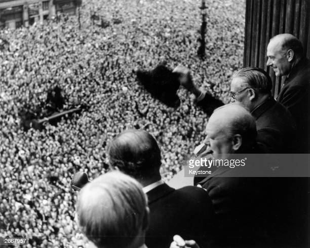British Prime Minister Winston Churchill waving to crowds gathered in Whitehall on VE Day 8th May 1945