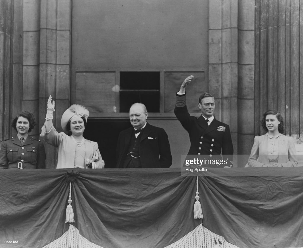 British prime minister Winston Churchill (1874 - 1965) (centre) with Queen Elizabeth, King George VI (1895 - 1952), Princess Elizabeth (left) and Princess Margaret Rose (1930 - 2002) waving from the balcony of Buckingham Palace during VE Day celebrations.