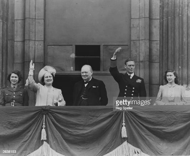 British prime minister Winston Churchill with Queen Elizabeth King George VI Princess Elizabeth and Princess Margaret Rose waving from the balcony of...