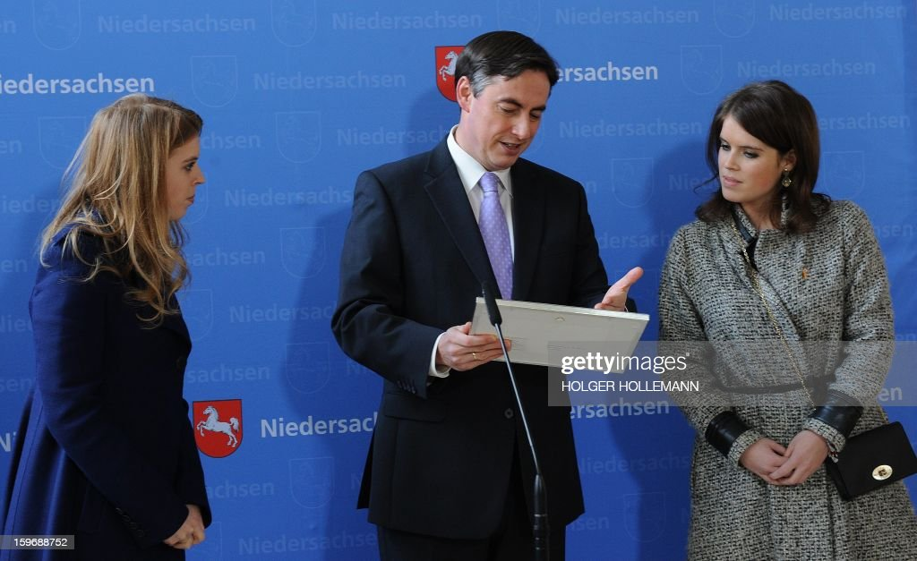 British princesses Beatrice (L) and Eugenie (R) of York receive historic prints of castle Hanover-Herrenhausen from Premier of Lower Saxony David McAllister (CDU) at the state chancellery in Hanover, on January 18, 2013. After the official welcome the princesses attended the ceremonial opening of the rebuilt castle Hanover-Herrenhausen.