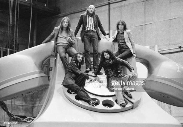 British progressive rock band Gentle Giant posing on a giant model of a telephone UK 1974 Clockwise from top centre drummer John Weathers bassist Ray...