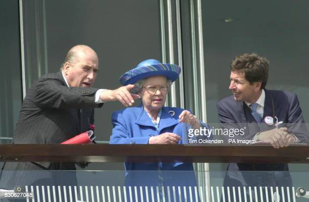 British Queen Elizabeth II talks with her horse racing advisors as she attends the Vodafone Derby meeting at Epsom in Surrey