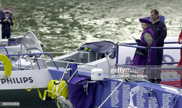 British Queen Elizabeth II watches as the champagne smashes over the anchor of the Team Philips catamaran in the shadow of Tower bridge in London The...