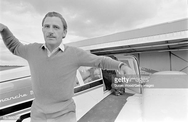 British racecar driver and team owner Graham Hill hops off the wing of a private plane at an unidentfied airfield England January 1970