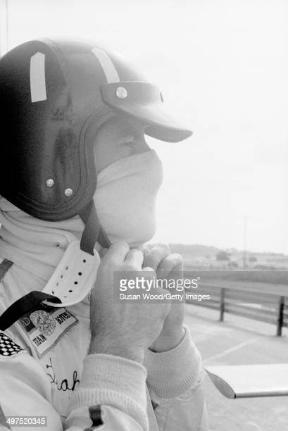 British racecar driver and team owner Graham Hill puts on his helmet before a race England January 1970