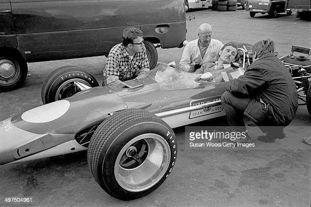 British racecar driver and team owner Graham Hill sits behind the wheel as he inspects his Formula One car England January 1970