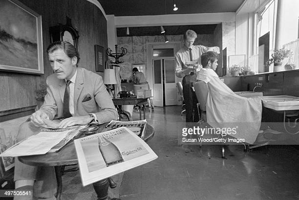 British racecar driver and team owner Graham Hill waits his turn in a barber's shop London England January 1970