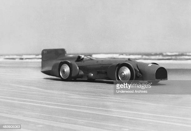 British racer Captain Malcolm Campbell in his Bluebird race car setting a new auto speed record of 245 mph to shatter the old one of 231 mph by Major...