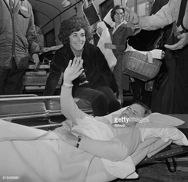 British racing driver and team owner Graham Hill is carrried from an airplane accompanied by his wife Bette on arrival from America to London Airport...