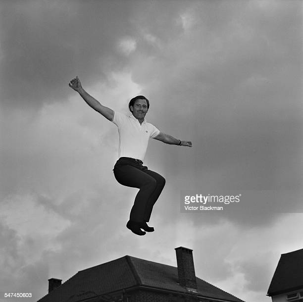 British racing driver Graham Hill on a trampoline he has installed in his garden at home 4th July 1967