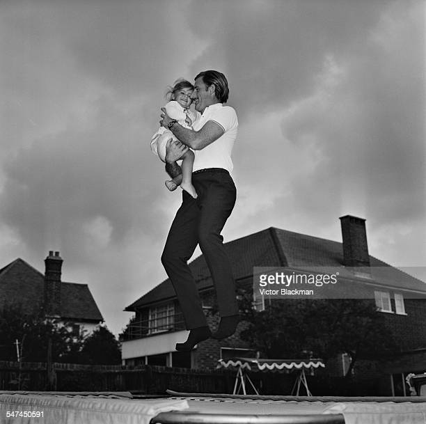 British racing driver Graham Hill with his daughter Samantha on a trampoline he has installed in his garden at home 4th July 1967