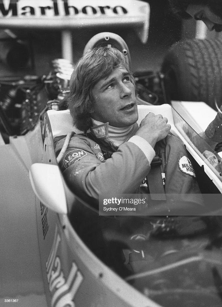 British racing driver James Hunt sitting inside a Formula 1 racing car before a race