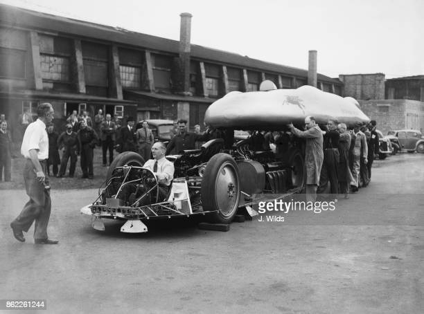 British racing driver John Cobb sits in the cockpit of the Railton Special at Brooklands UK while the body of the vehicle is lowered onto the chassis...
