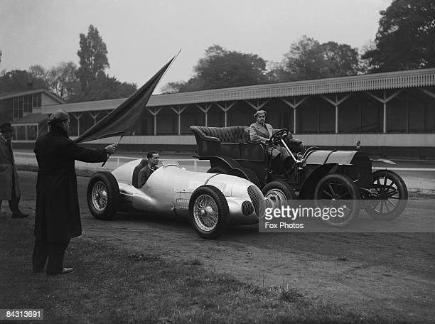 British racing driver Richard Seaman driving a Mercedes racecar alongside Herr Heck in a 1903 Mercedes at Crystal Palace 7th October 1937 They are...
