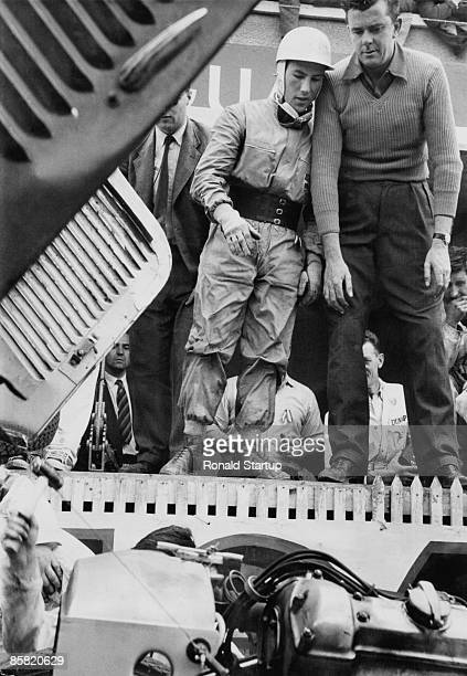 British racing driver Stirling Moss explains a problem to his team manager Lofty England in the Jaguar pits during the Le Mans 24 Hour Race at the...