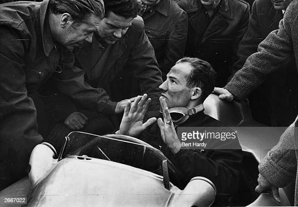 British Racing driver Stirling Moss is questioned by the Mercedes Benz team experts after his trial run in one of the cars The man on the left is...