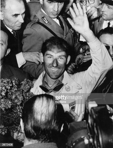British racing driver Stirling Moss waves for the cameras after winning the Italian Mille Miglia Race setting a new record
