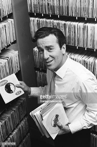 British radio and TV presenter and sports commentator Kent Walton taking 45 rpm singles records from the shelves in a gramophone library London circa...
