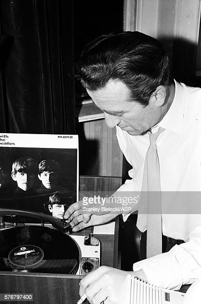 British radio and TV presenter and sports commentator Kent Walton plays the Beatles album 'With The Beatles' in a London office circa 1965