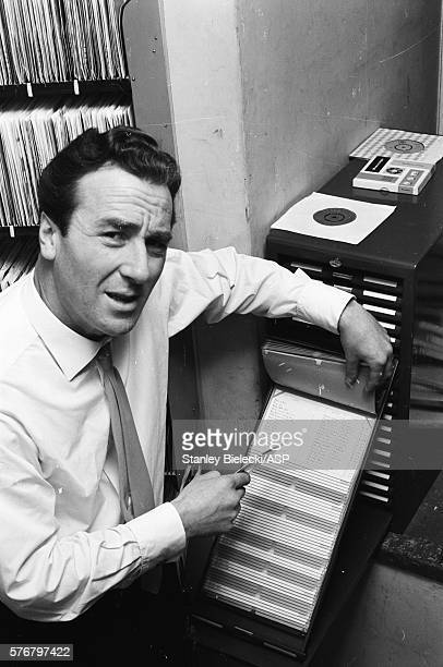 British radio and TV presenter and sports commentator Kent Walton checking the card index in a gramophone library London circa 1965
