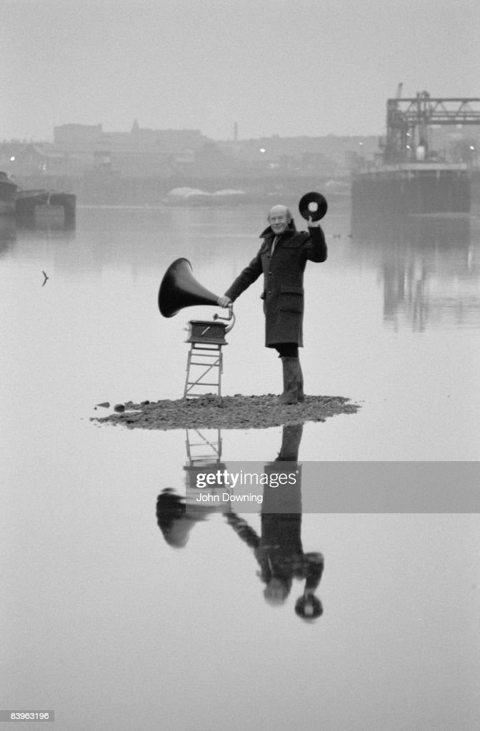 British radio broadcaster Roy Plomley (1914 - 1985) with an old-fashioned gramophone on a patch of dry land in the Thames near the bottom of his garden, 19th January 1982. Desert Island Discs.