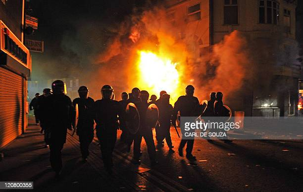 British riot police arrive in front of a burning building in Croydon South London on August 8 2011 Now in it's third night of unrest London has seen...