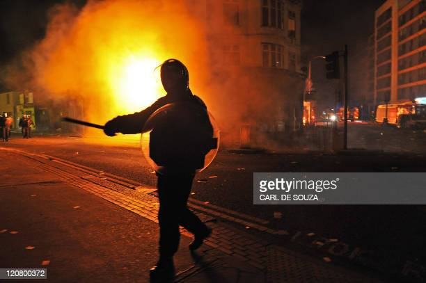 A British riot policeman gestures in front of a burning building in Croydon South London on August 8 2011 Now in it's third night of unrest London...
