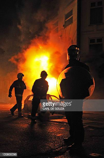 A british riot policeman stands guard as firemen arrive in front of a burning building and burnt out car in Croydon South London on August 8 2011 Now...