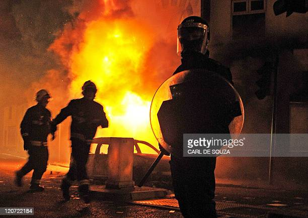 A British riot policeman stands guard in front of a burning building and burnt out car in Croydon South London on August 8 2011 Now in it's third...