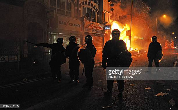 British riot policemen stand in front of a burning building in Croydon South London on August 8 2011 Now in it's third night of unrest London has...