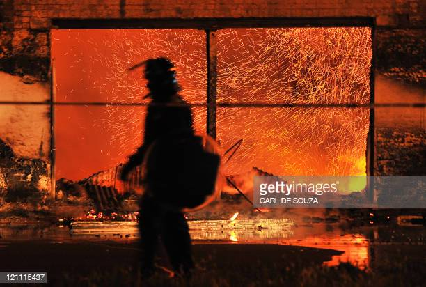 A British riot policemen walks past a burning 140 year old furniture store in Croydon South London on August 8 2011 Now in it's third night of unrest...
