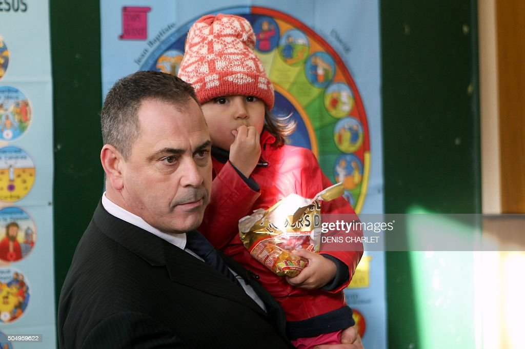 British Robert Lawrie carries fouryearold Afghan refugee Bahar Ahmadi on January 14 2016 in BoulognesurMer prior to the start of his trial for trying...