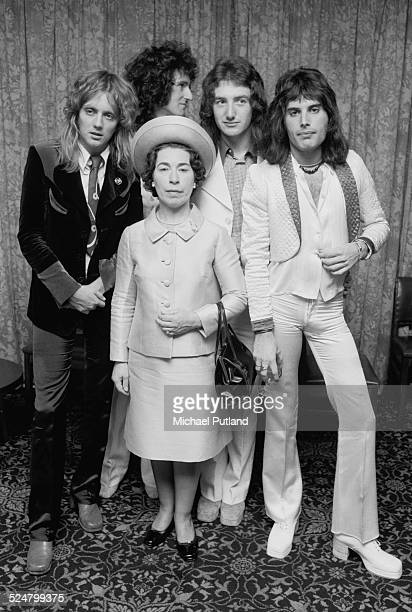 British rock band Queen posing with actress and Queen Elizabeth II lookalike Jeannette Charles September 1974 The group are drummer Roger Taylor...
