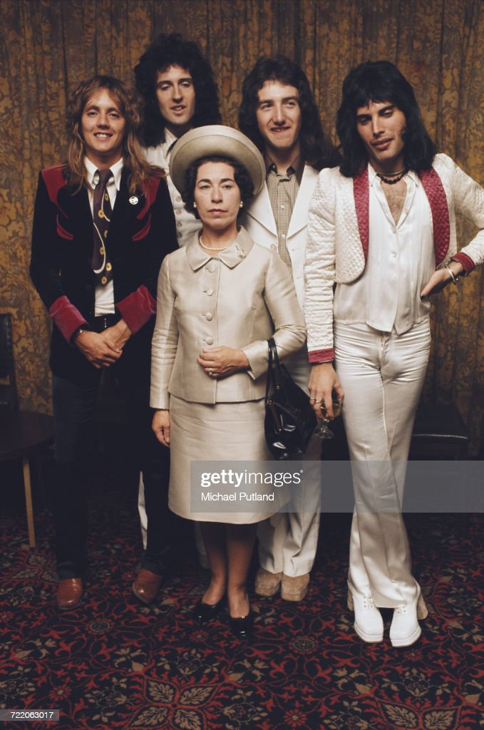 British rock band Queen posing with actress and Queen Elizabeth II look-alike, Jeannette Charles, September 1974. The group are (left to right) drummer Roger Taylor, guitarist Brian May, bassist John Deacon and singer Freddie Mercury (1946 - 1991).