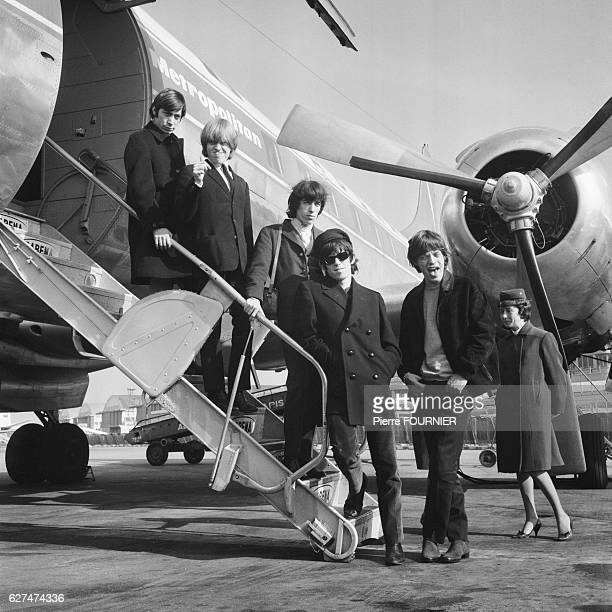 British rock band The Rolling Stones, with members Charlie Watts (drums), Brian Jones (guitar), Bill Wyman (bass), Keith Richards (lead-guitar) and Mick Jagger (vocals), arriving at the airport.