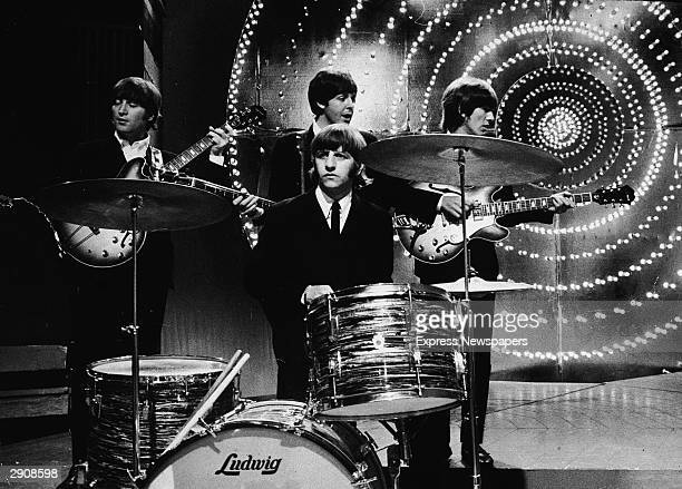 British rock group The Beatles perform live on stage in front of a circular lit backdrop at the BBC TV Centre June 1966 LR Guitarist John Lennon...