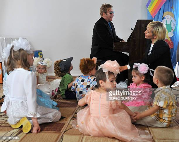 British rock legend Sir Elton John plays a song on a piano for patients of a specialized orphanage for HIVpositive children after the first results...