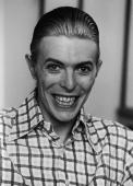 British rock singer and actor David Bowie grins broadly wearing a plaid shirt with his hair slicked back circa 1980