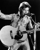 British rock singer David Bowie performs with an acoustic guitar on stage in costume as 'Ziggy Stardust' circa 1973