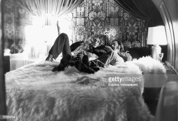 British rock singer Robert Plant of the band Led Zeppelin and the group's road manager Richard Cole relax on a bed covered by a fur rug and discuss...