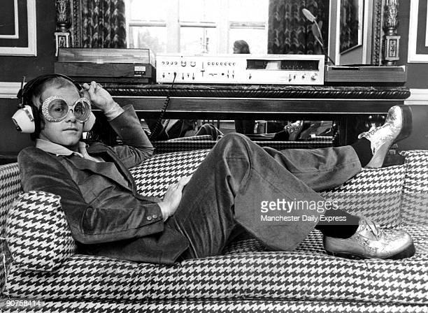 British rock star Elton John listening to music on Sony hifi equipment