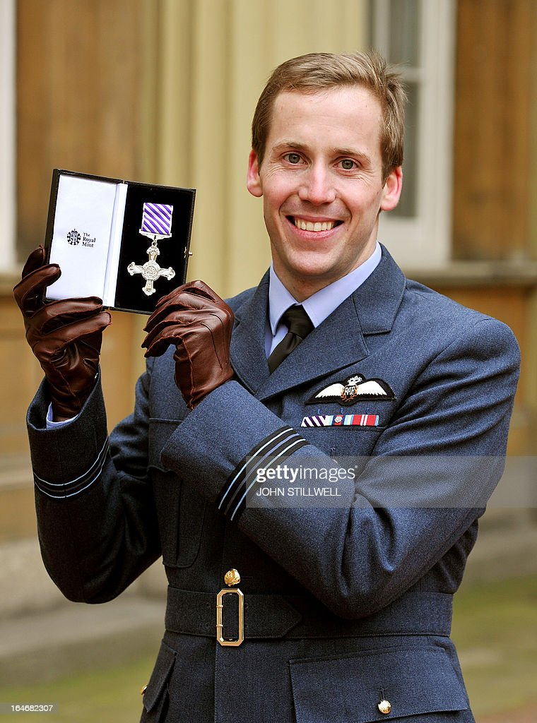 British Royal Air Force Flight Lieutenant Gerald Wyatt holds his award of a Distinguished Flying Cross for showing great courage in the face of the enemy in Afghanistan during an investiture ceremony by Britain's Queen Elizabeth II at Buckingham Palace in central London on March 26, 2013. AFP PHOTO / POOL / JOHN STILLWELL
