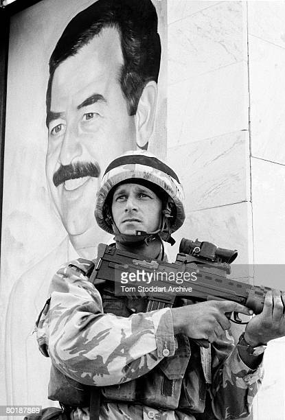 British Royal Marine Corporal Alun Jones of 42 Commando takes up a defensive position by a mural of Iraqi leader Saddam Hussein in Basra on the day...