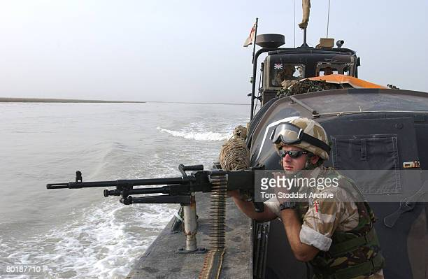 A British Royal Marine of 539 Assault Squadron trains his machine gun on the marshes near Basra in case of ambush while on patrol during the first...
