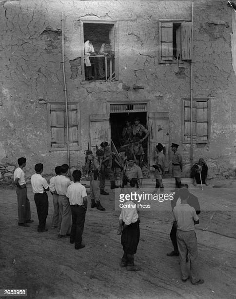 British Royal Marines carrying out an early morning arms search in a suspected EOKA hideout in the mountain village of Akantmou watched by villagers